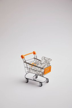 Close up view of shopping cart with little goods made of paper on grey background stock vector
