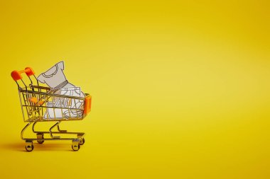 close up view of little shopping trolley with paper clothes on yellow backdrop