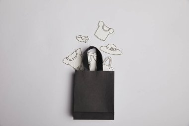 top view of black shopping bag and paper clothes on grey background, shopping concept