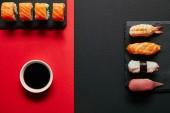 plochý lay se sójovou omáčkou v misce, Suši nastaví na černé břidlicové desky v červené a černé pozadí