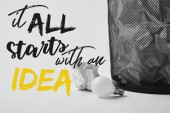 Photo light bulb with crumpled papers in office trash bin on white with it all starts with an idea inspiration