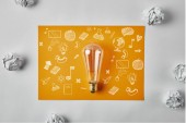 Photo top view of incandescent lamp on blank yellow paper with business icons surrounded with crumpled papers on white surface