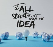 light bulb with crumpled papers on blue surface with it all starts with an idea inspiration