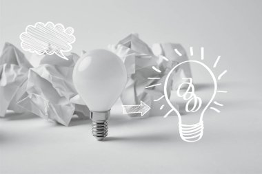 White light bulb with drawn light bulb sign on background with crumpled papers stock vector