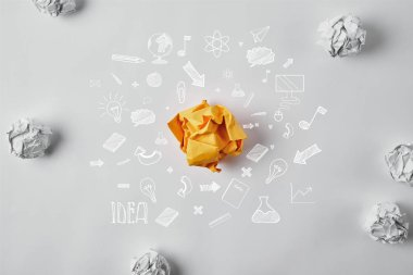 top view of crumpled yellow paper surrounded with business idea icons and white crumpled papers on white surface