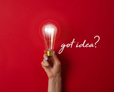 woman holding vintage incandescent lamp on red surface with