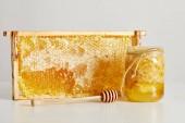 Fotografie zblízka pohled dřevěných medu hlubší, sklenice s medem a zásobníku z včelího vosku na bílém stole
