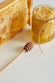 zblízka pohled dřevěných medu hlubší, sklenice s medem a zásobníku z včelího vosku na bílém stole