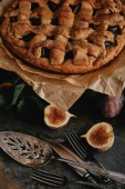 Photo close up view of homemade pie on baking paper, antique cutlery and fresh figs on dark tabletop