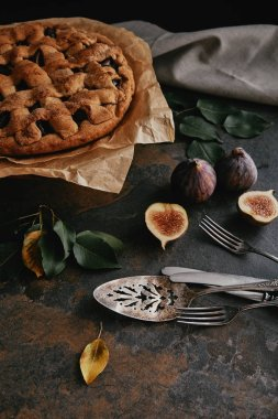 close up view of homemade pie on baking paper, antique cutlery and fresh figs on dark tabletop