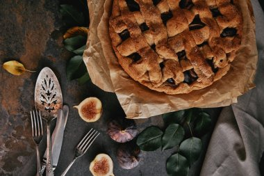 flat lay with homemade pie on baking paper, antique cutlery and fresh figs on dark tabletop