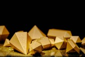 glänzende, facettierte Goldstücke und Staub auf schwarzem Hintergrund