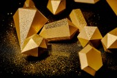 close-up view of shiny golden pieces and dust on black