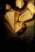 top view of shiny golden pieces and dust on black