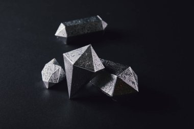high angle view of shiny faceted silver pieces on black