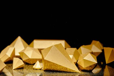 close-up view of shiny faceted pieces of gold and golden dust reflected on black