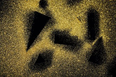 black shapes on golden glittering background
