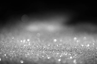 abstract blurred glowing silver glitter on dark background