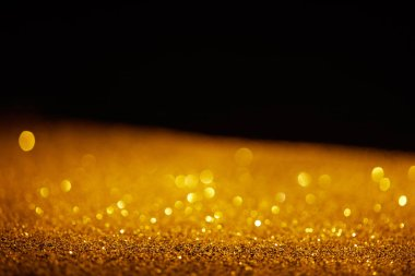 Blurred golden glowing glitter on black background stock vector