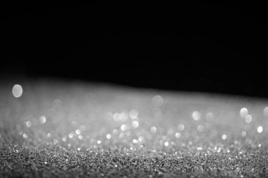 Blurred silver glowing glitter on black background stock vector