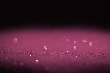 sparking purple glitter with bokeh on black background