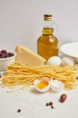Fotografie  close up view of arranged ingredients for cooking italian pasta on white tabletop