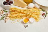 Photo  close up view of arranged ingredients for cooking italian pasta on white tabletop