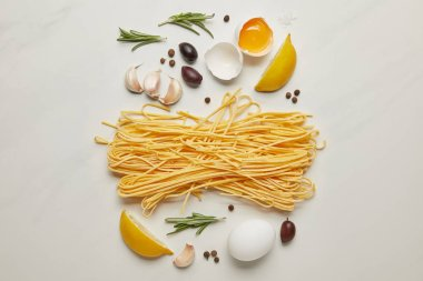 flat lat with assorted italian pasta ingredients arranged on white marble surface