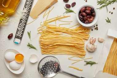 Flat lay with italian pasta ingredients, ladle and grater arranged on white tabletop stock vector
