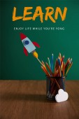 Photo colorful pencils, rocket, cloud sign on wooden table with chalkboard on background with learn - enjoy life while you are young lettering