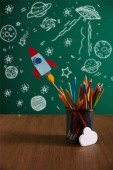 Photo colorful pencils, rocket, cloud sign on wooden table with chalkboard on background with universe icons