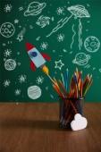 színes ceruza, rakéta, felhő jele a fából készült asztal és a háttér ikonok univerzum chalkboard