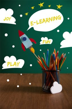 Colorful pencils, rocket, cloud sign on wooden table with chalkboard on background with play, joy, fun and e-learning words stock vector