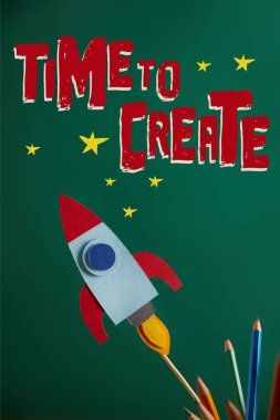 Pencils and colorful rocket on green chalkboard with
