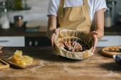 Fotografie cropped shot of woman holding baking form with sliced figs over rustic wooden table