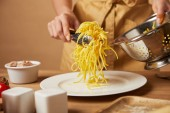 Fotografie cropped shot of woman putting spaghetti on plate from colander