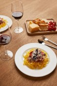 Fotografie close-up erschossen Teller Spaghetti mit Rotwein in Gläsern auf Holztisch