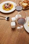 Fotografie close-up erschossen der Platten der leckeren Pasta mit Rotwein in Gläsern auf Holztisch