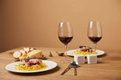 Fotografie Teller mit leckeren Pasta mit Rotwein in Gläsern auf Holztisch