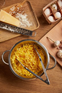 top view of spaghetti in metal colander surrounded with ingredients for pasta on wooden table
