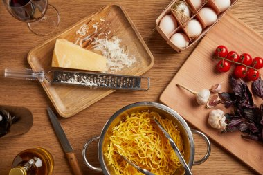 top view of spaghetti in metal colander surrounded with various ingredients for pasta on wooden table