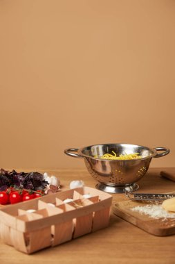 spaghetti in metal colander surrounded with ingredients for pasta on wooden table