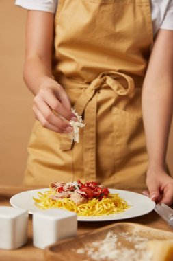 cropped shot of woman in apron spilling grated cheese onto pasta in plate