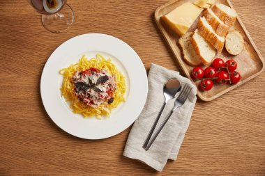 top view of plate of pasta with red wine on wooden table