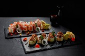 Photo close-up view of delicious fresh traditional sushi rolls on slate boards