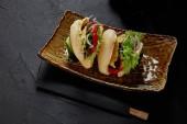 Fotografia vista ravvicinata dei deliziosi panini freschi con le verdure sul piatto e bacchette