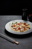 Fotografia piatto giapponese gourmet con filetti di pesce e avocado in salsa sulla banda nera