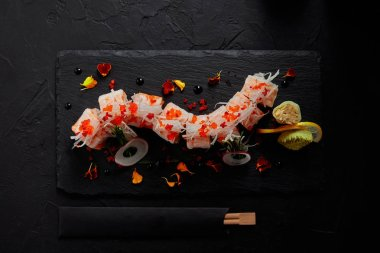 top view of yummy roll in mamenori with shrimp, salmon and avocado on slate board and chopsticks