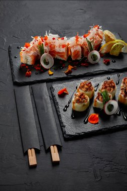 delicious fresh sushi rolls on slate boards and chopsticks