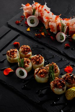 close-up view of roll in mamenori with shrimp, salmon and avocado in sauce nigiri and roll with creamy eel and kimchi mayonnaise